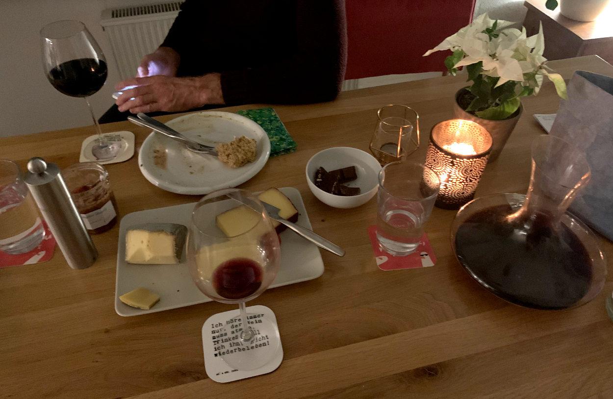 Tisch nach dem Essen, mit Käse, Weingläsern, Dekantierer, Kerze, diversen Leckereien. Sieht gemütlich aus.