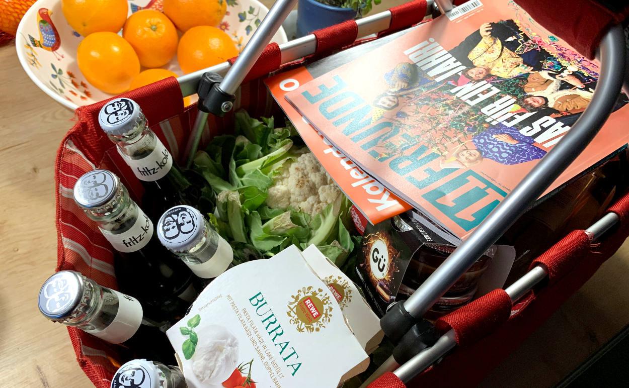 Einkaufskorb mit Limo, 11 Freunde, Burata, Blumenkohl, im Hintergrund Orangen.