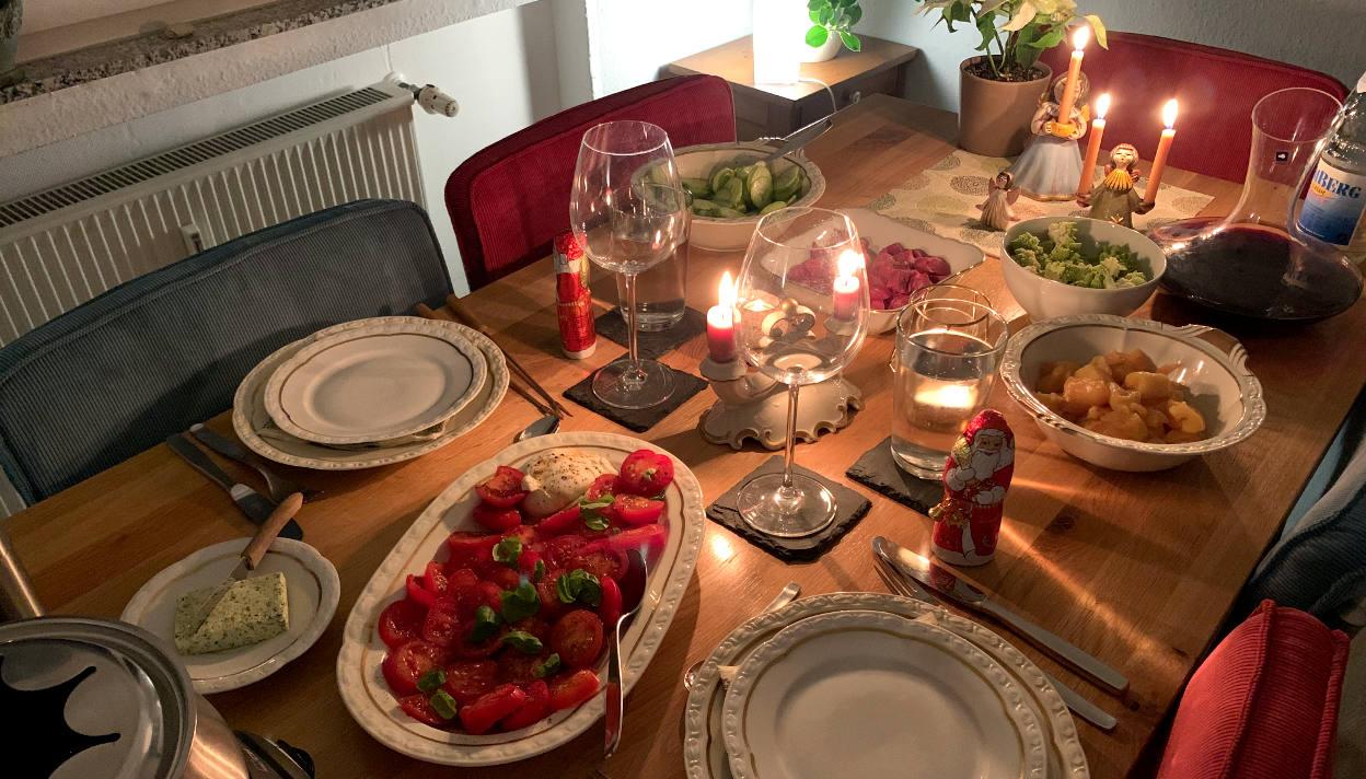 Gedeckter Tisch mit Kerzen. Darauf Tomate-Mozzarella, ein Fonduetopf, Gurkensalat und Fleisch.