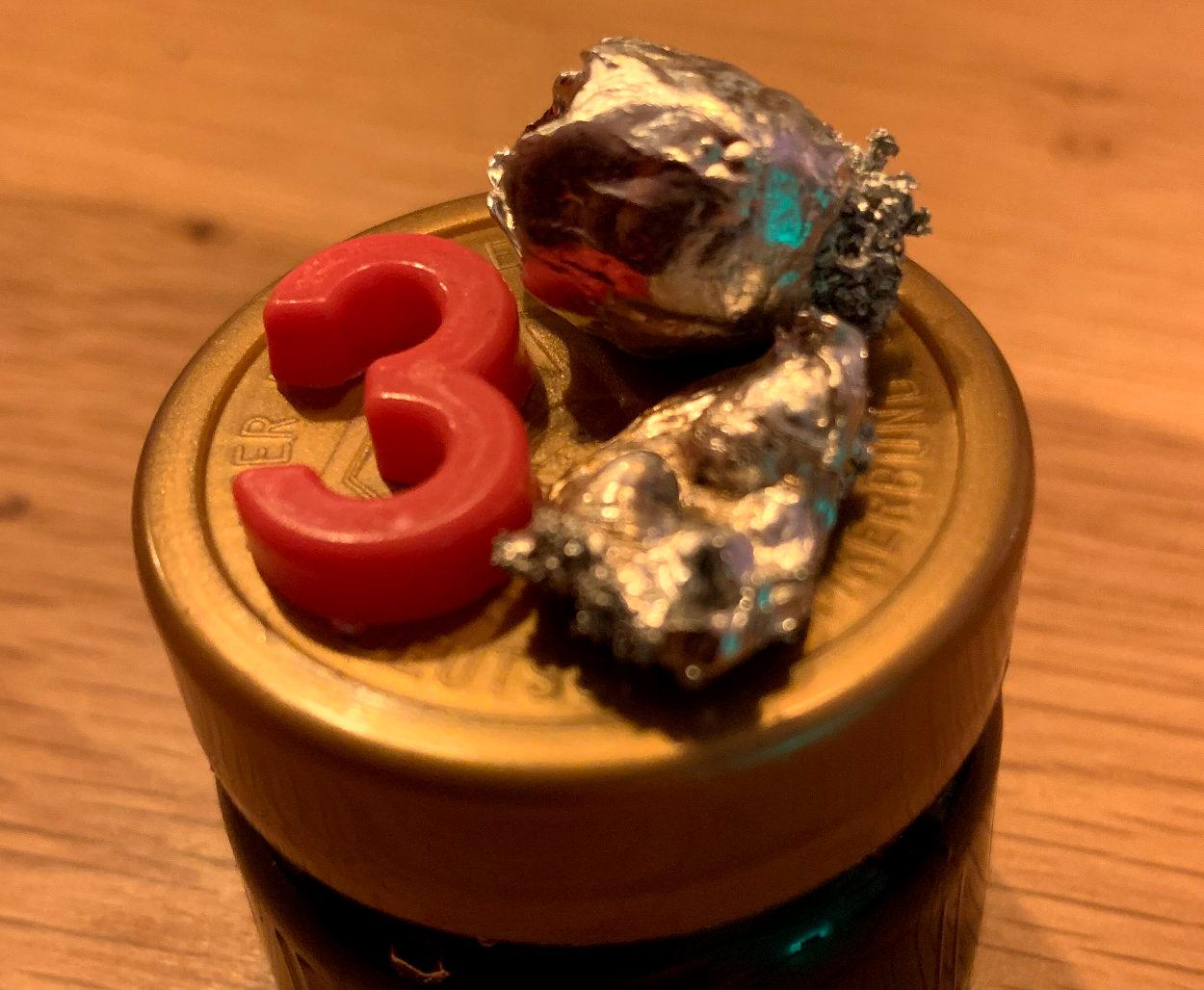 Ziffer Drei aus Plastik, daneben undefinierbare Zinngussteile.