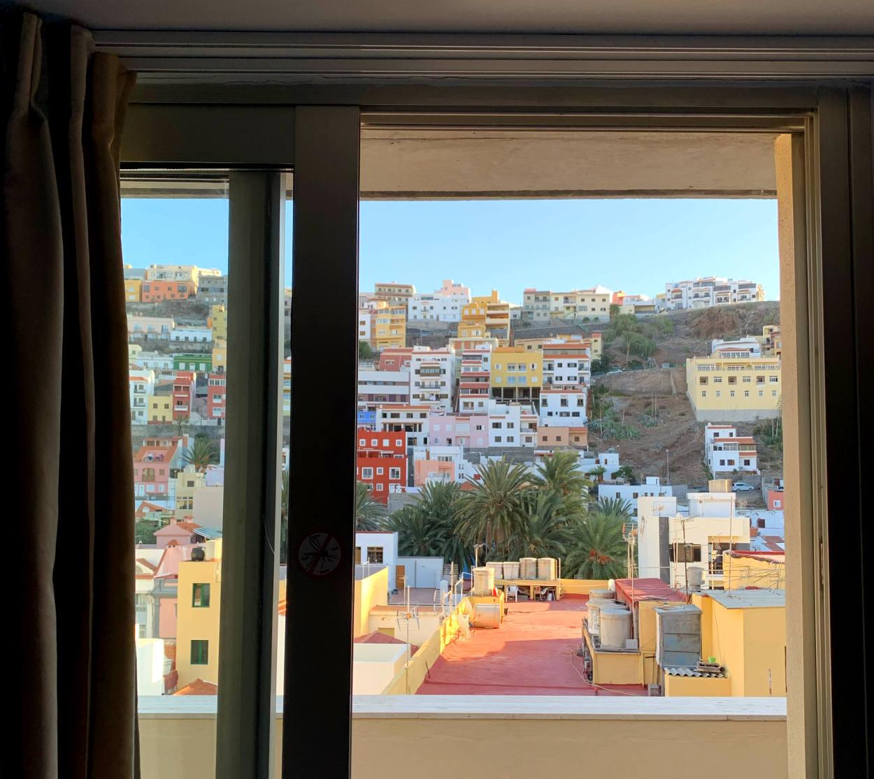 Blick auf einem Fenster auf bunte Häuser an einem Berghang. Die Sonne scheint.