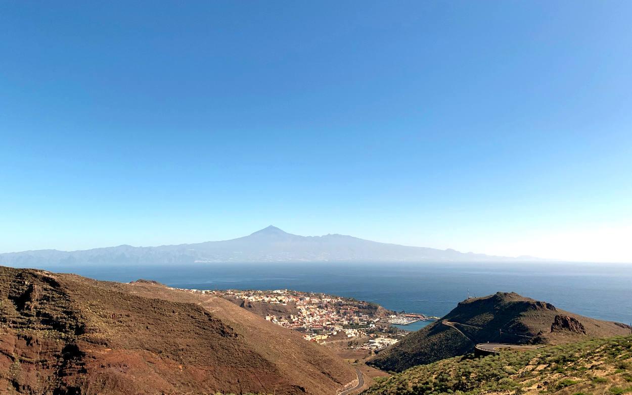 Blick von einem Aussichtspunkt in die Weite: karge Berge, eine Stadt am Meer, im Hintergrund die Insel Teneriffa.