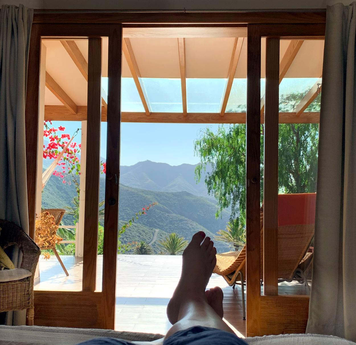 Füße, dahinter eine Terrassentür, dahinter grüne Berge und Sonnenschein.