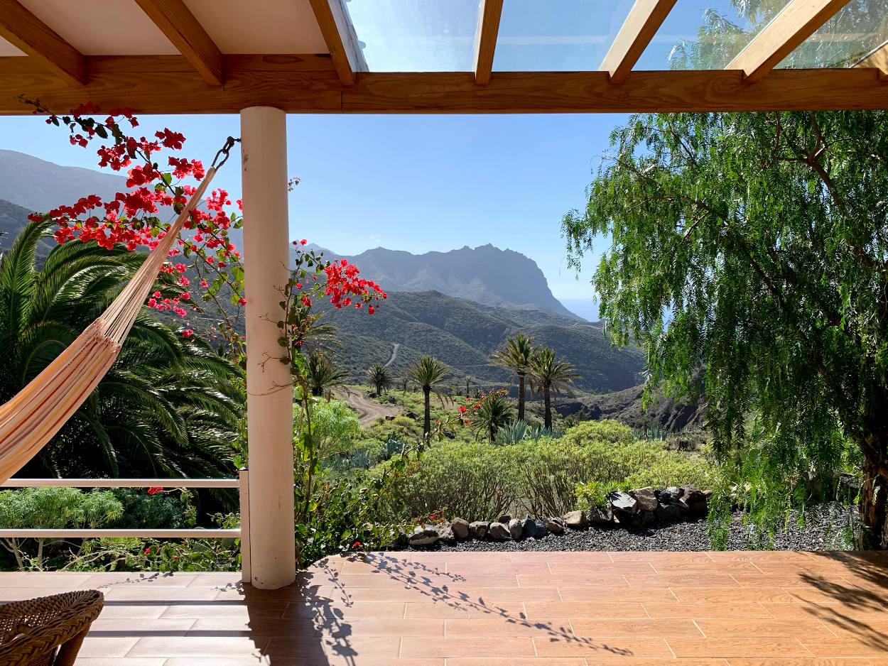 Überdachte Terrasse, Blick auf Berge, dahinter das Meer, eine Hängematte baumelt im Sonnenschein.