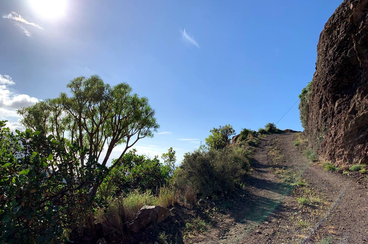 Pfad hinauf, führt rechts um einen Felsen herum