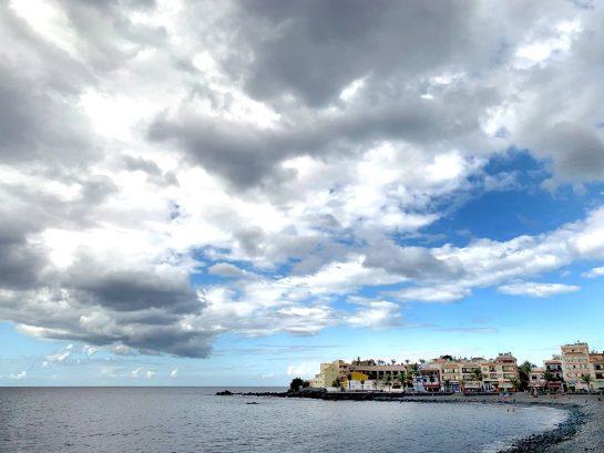 Küste, im Hintergrund ragt eine Landzunge mit Häusern ins Meer. Wolkenhimmel
