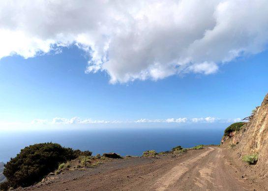 Erdiger Weg hoch über dem Abgrund, dahinter Horizont
