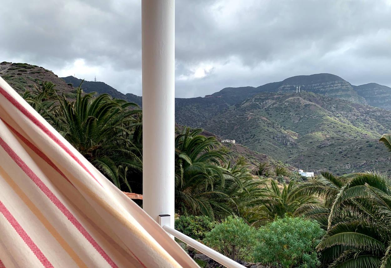 Ein Teil der Hängematte, dahinter grüne Berge, davor Palmen. Am Himmel Wolken.