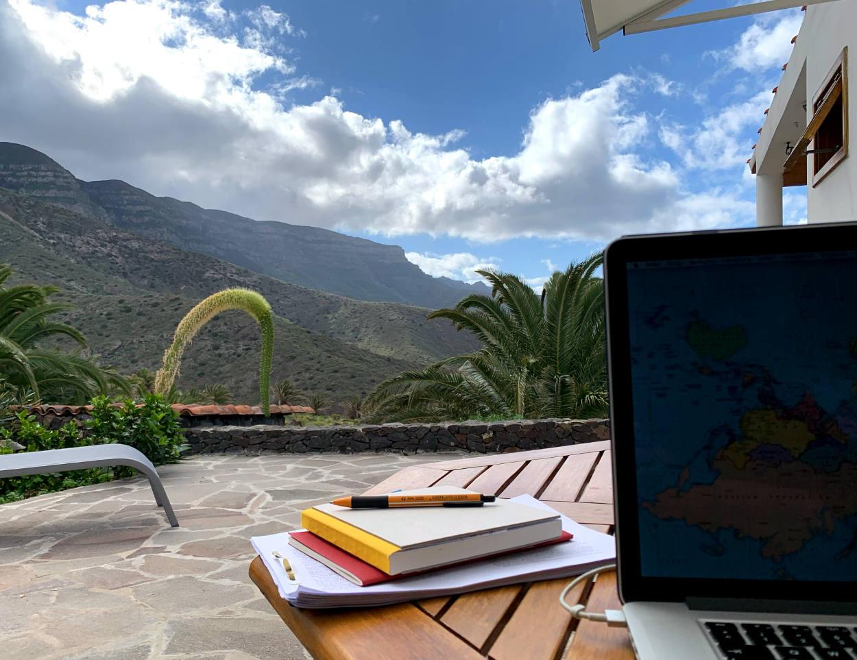 Laptop und Notizbücher auf Holztisch, im Hintergrund Palmen und Himmel mit Schäfchenwolken, Blick ins Tal