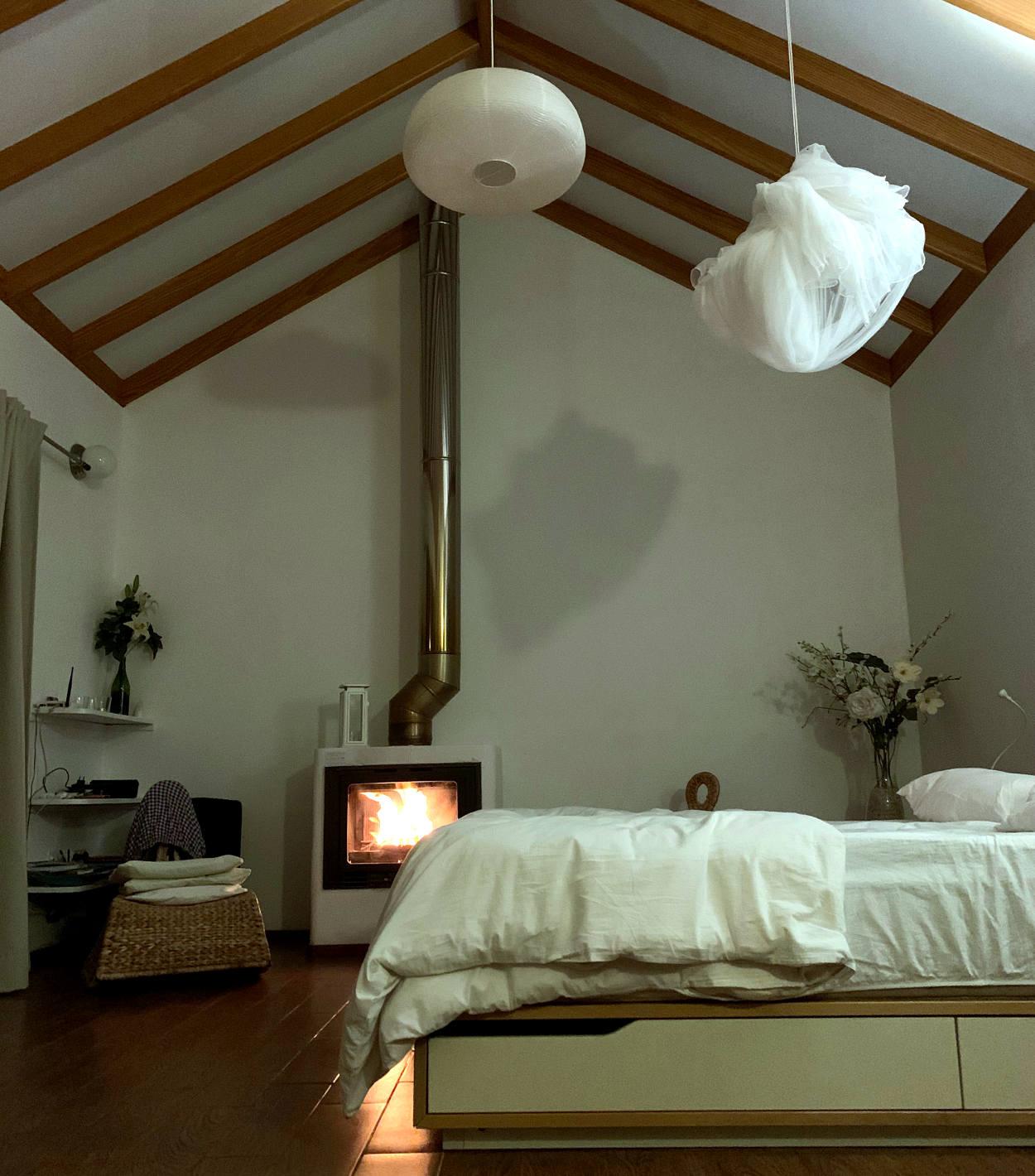 Hohes Zimmer, darin ein Bett, über dem eine Lampe und ein Moskitonetz hängen, dahinter ein Ofen, dessen Rohr zum Dach hinaus geht.