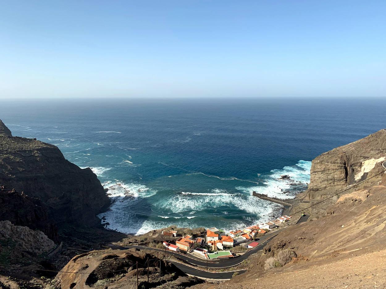 Blick aus der Höhe auf eine Bucht: einige Häuser, dahinter rollt das Meer an