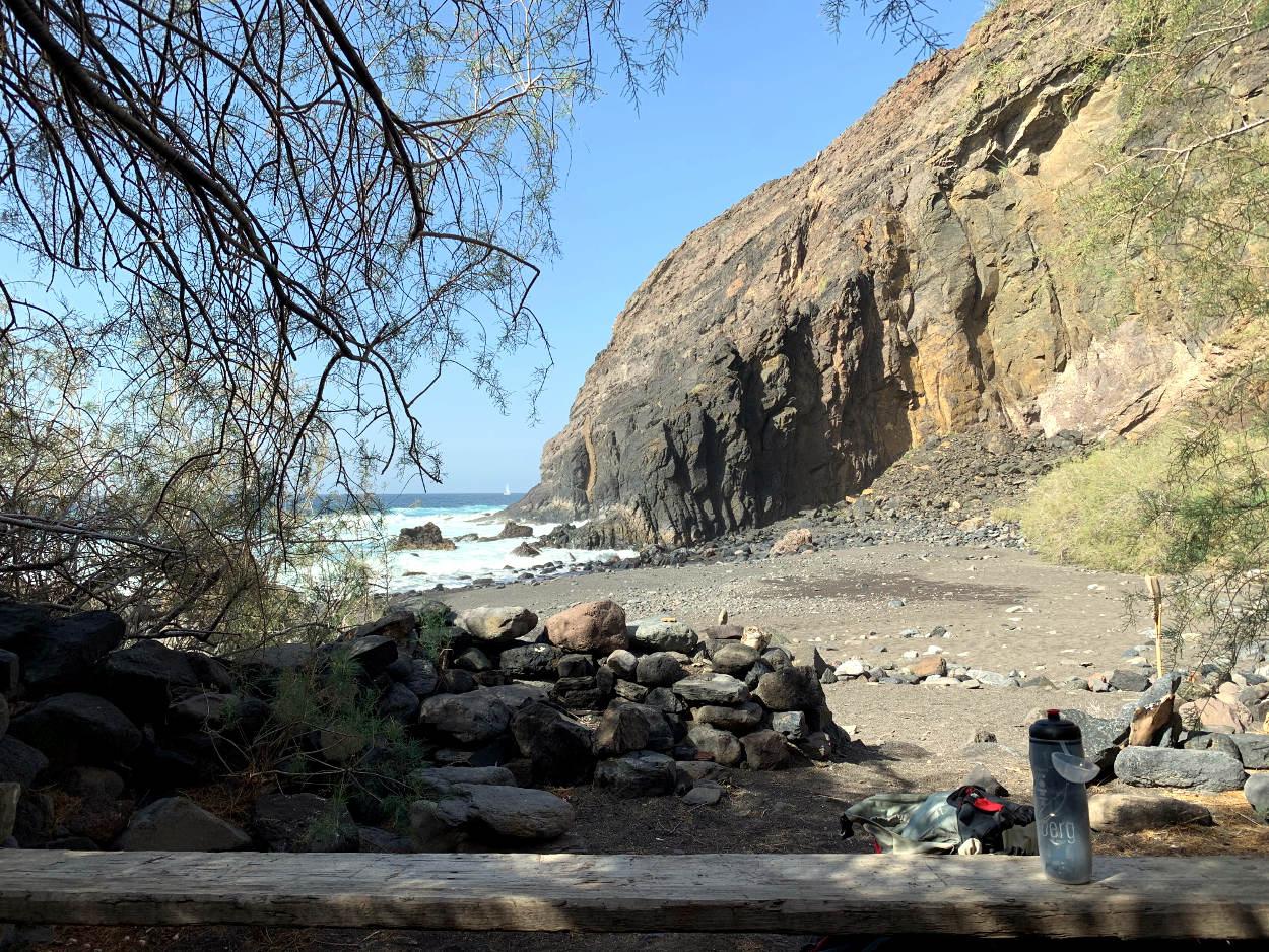 Holzbrett, darauf eine Trinkflasche, dahinter das Meer und Felsen, die ins Wasser abfallen