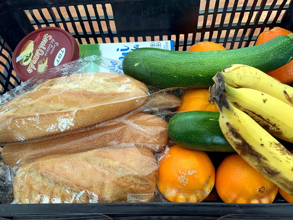 Ein Korb mit Zucchini, Orangen, Brot, einer Packung Milch, Bananen, Streichkäse