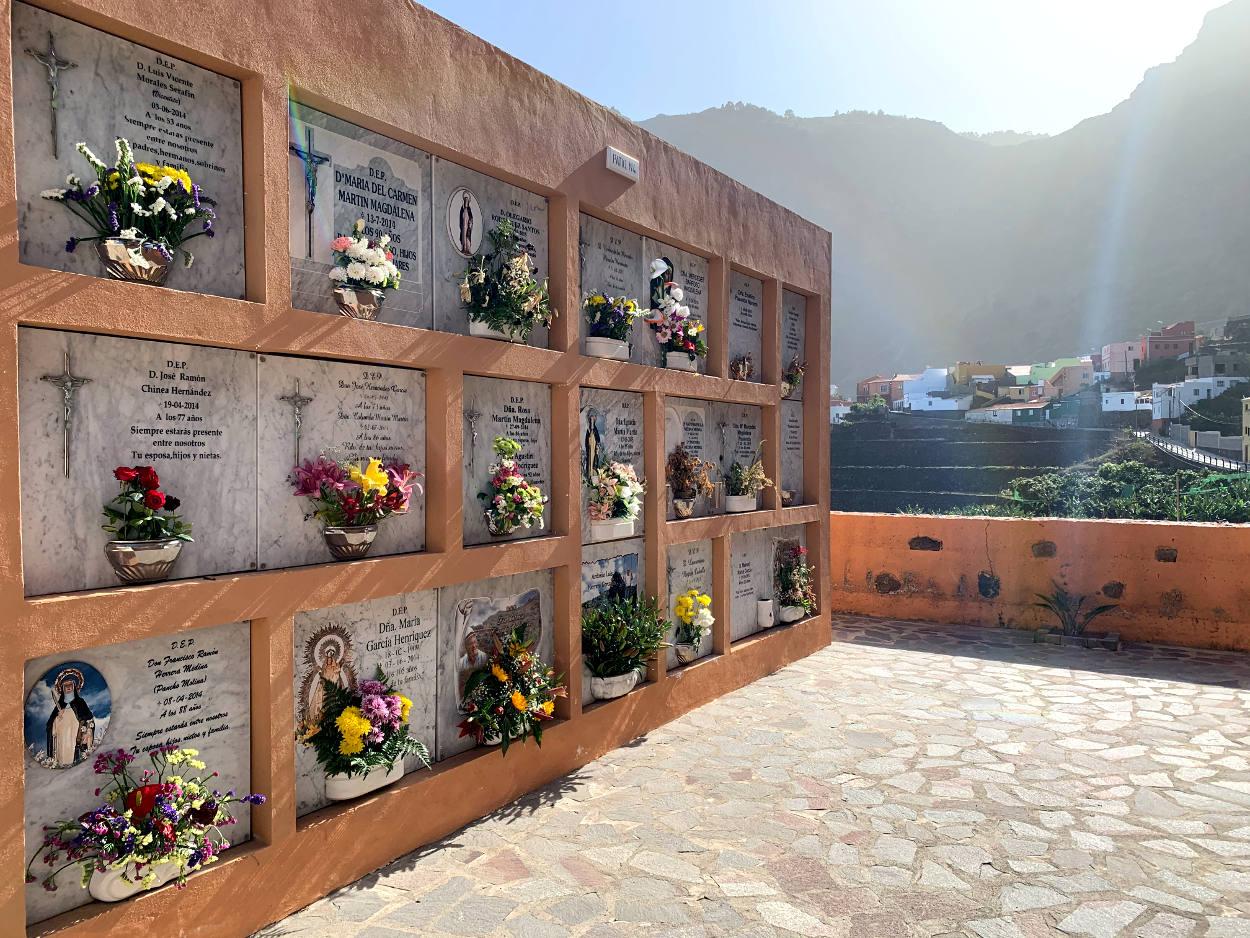 Friedhof: Kolumbarien mit Blumengestecken und Namen, im Hintergrund das Dorf