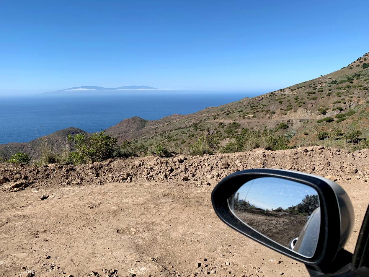 Im Vordergrund der Außenspiegel des Autos, Erdstraße und Bergrücken, in der Ferne eine Insel mit zwei Erhebungen