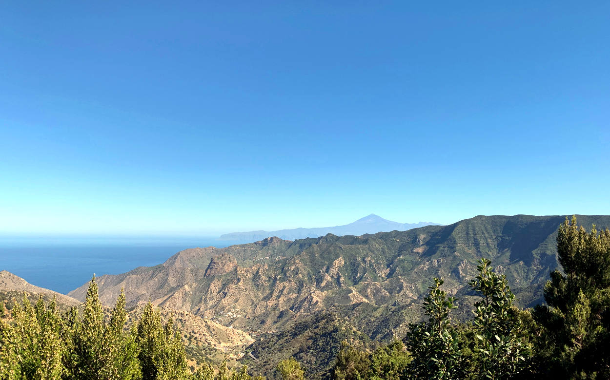Blick über eine Bergkette, in der Ferne Teneriffa mit dem Vulkankegel des Teide in der Mitte