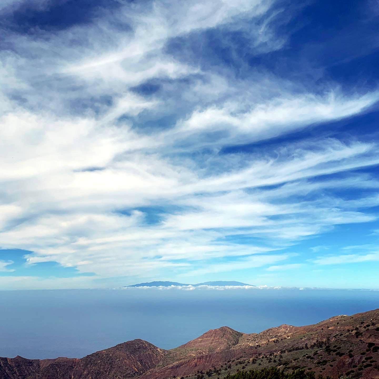 Insel mit zwei Erhebungen in der Ferne, wolkenverhangen. Im Himmel Schleierbewölkung.