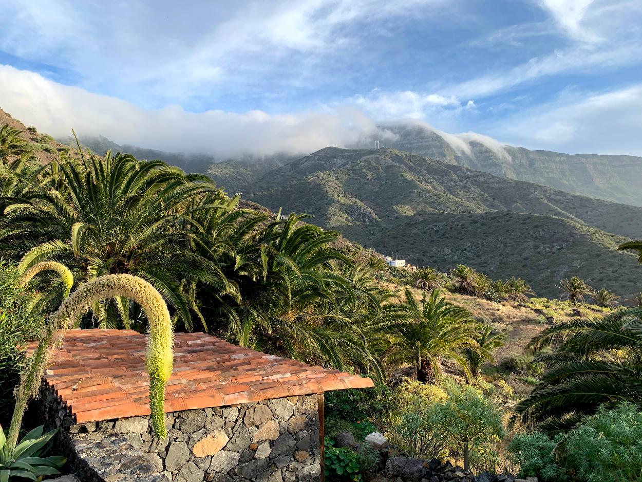 In der Ferne Berge, darüber liegen Wolken, die sich wie ein Wasserfall die Hänge hinabgießen.