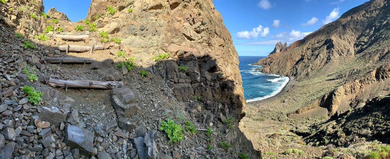 Links ein gestufter Weg, links, hinter einem Felsen, ist noch das Meer zu sehen.