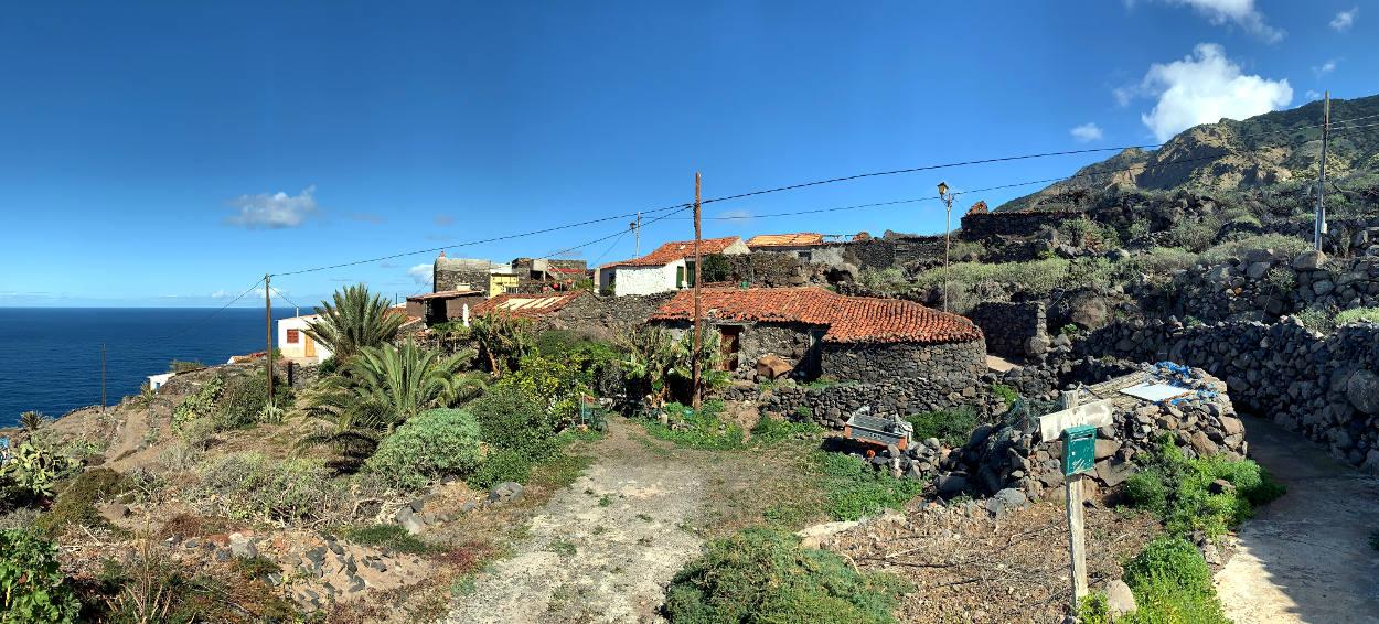 Hof aus mehreren sich zusammenduckenden Steinhäusern an der Kante zum Meer