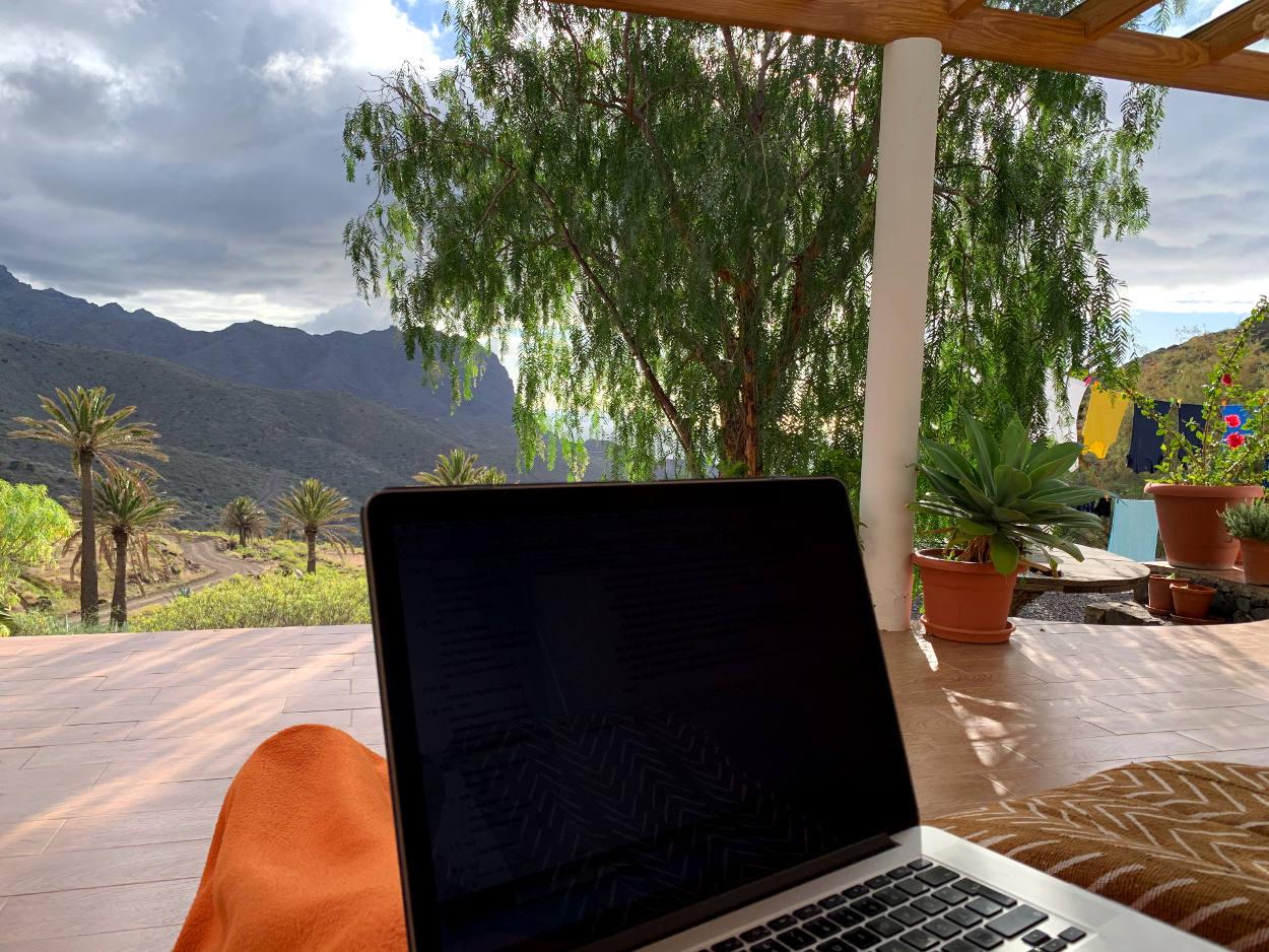Laptop auf den Knien, im Hintergrund das Tal, wolkiger Himmel, Wäsche auf der Leine
