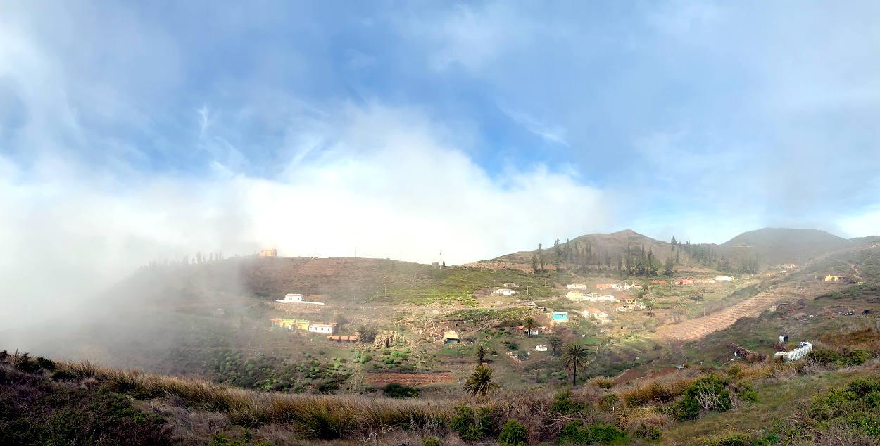 Dorf in den Berg, teilweise verschleiert von Wolken