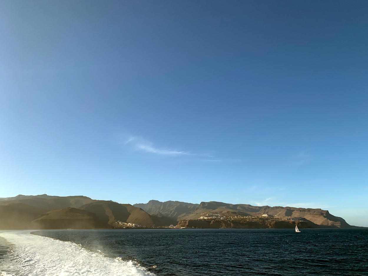Insel vom Schiff aus, davor ein Segelboot