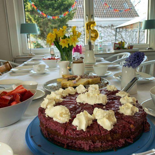 Kirsch-Buttercremetorte, dahinter ein  gedeckter Tisch, Frühlingsblumen, Girlanden am Fenster