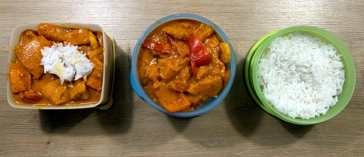 Drei Tupperdosen mit orangenem. stückigen Essen und Reis
