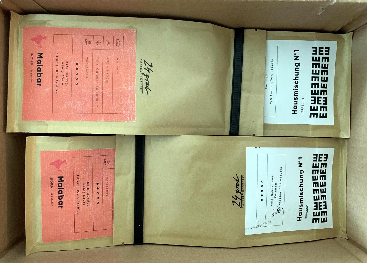 """Vier Pakete gemahlener Kaffee. Aufschriften: """"Hausmischung No 1"""" und """"Malabar""""."""