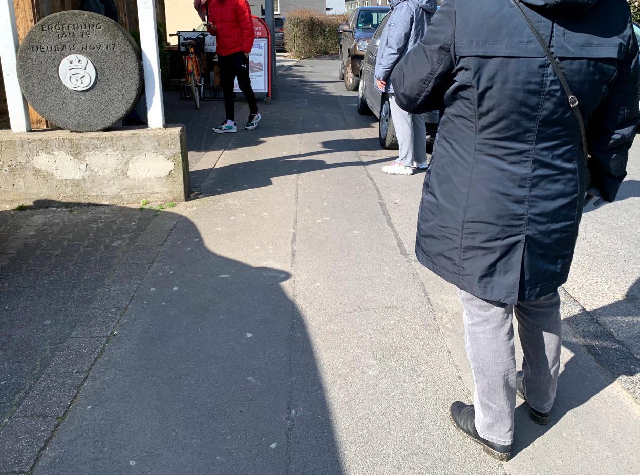 Drei Menschen in der Schlange auf dem Bürgersteig, weiter Abstand.