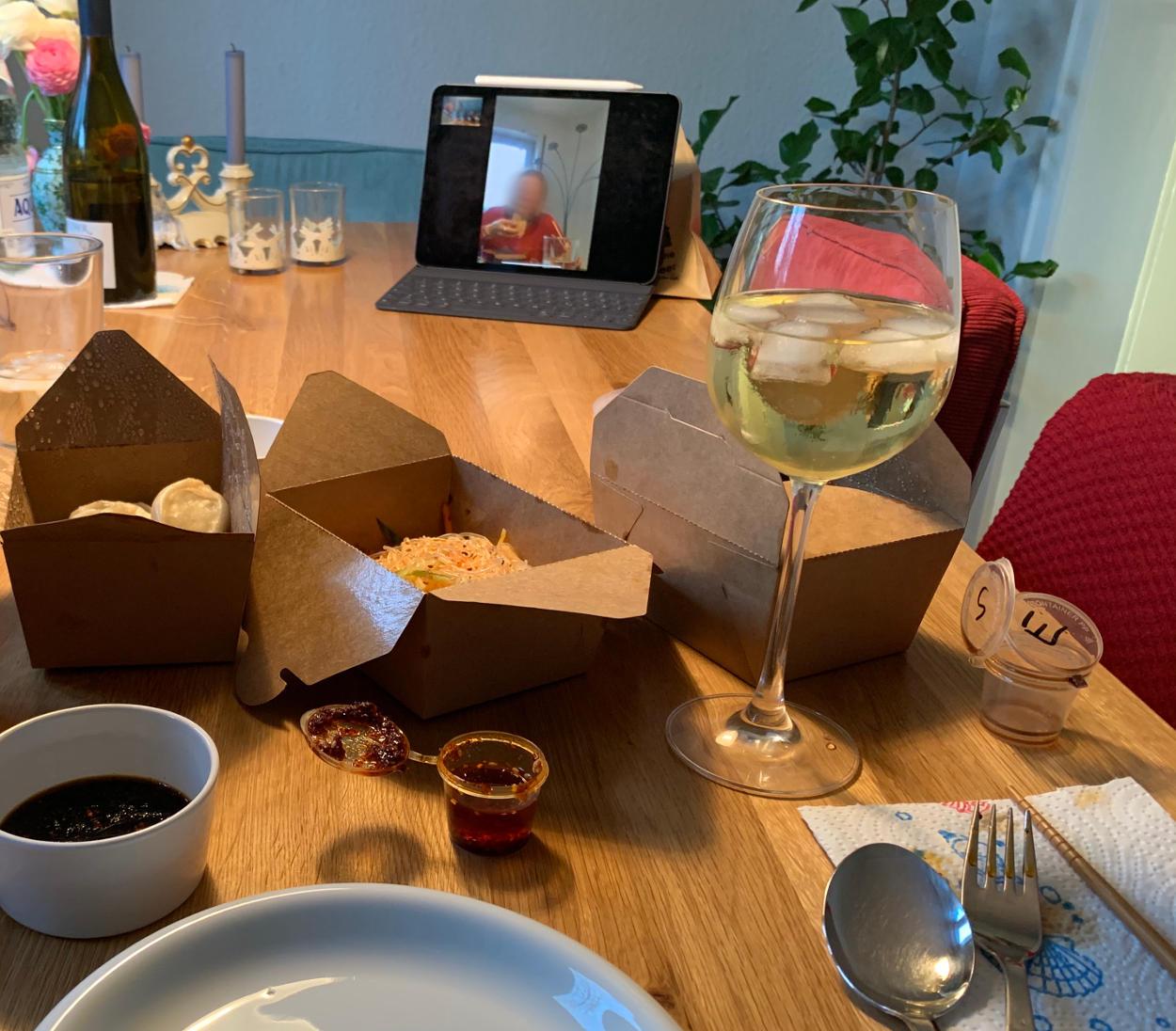 Esstisch, darauf Kartons mit Salat und Teigtaschen, am Ende des Tisches in iPad mit Facetime.