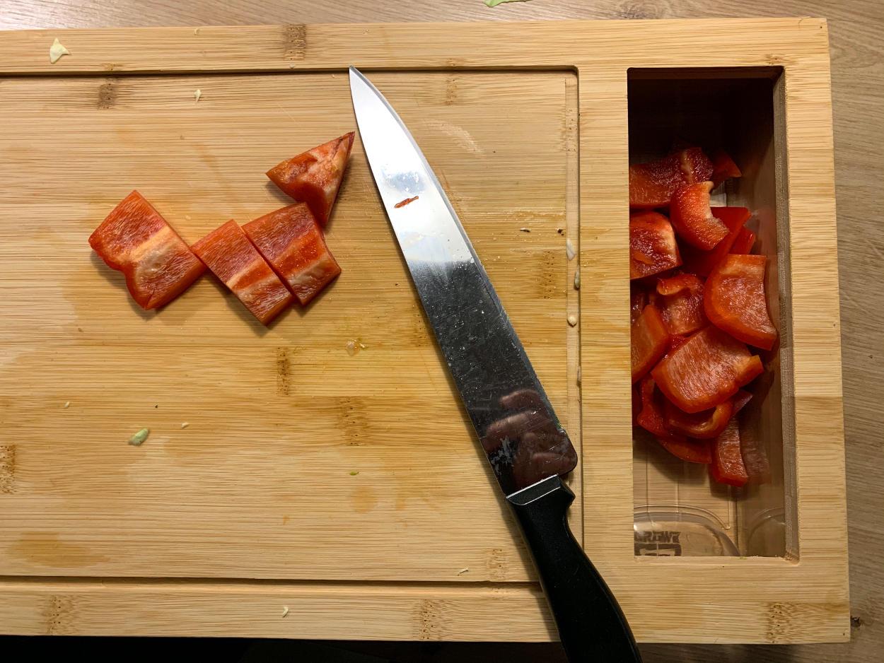 Brett mit Messer und geschnittener Paprike, rechts Schublade
