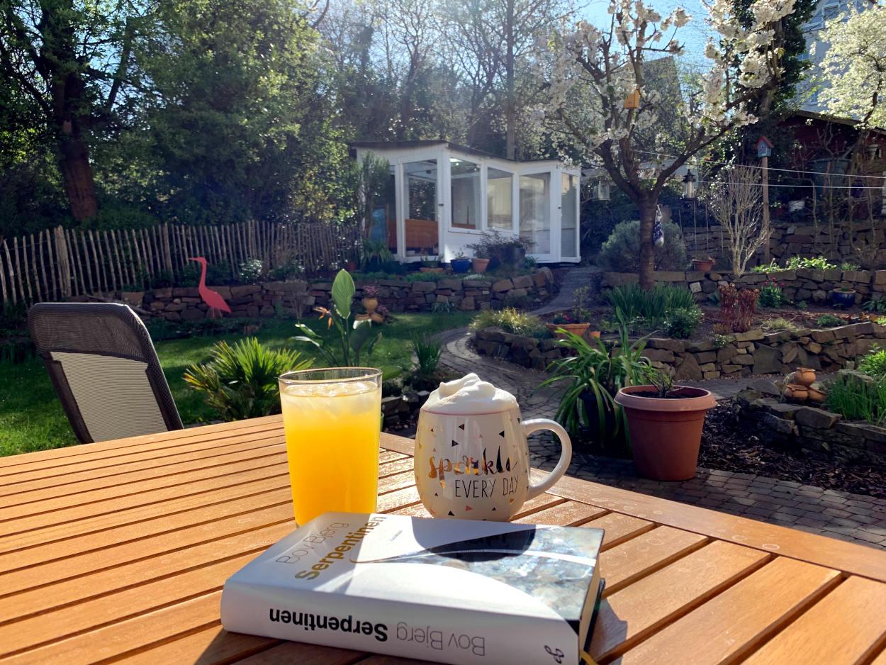 """Buch """"Serpentinen"""" auf dem Terrassentisch mit Milchkaffee und Saftschorle, dahinter der Garten mit blühendem Kirschbaum und Gewächshaus"""