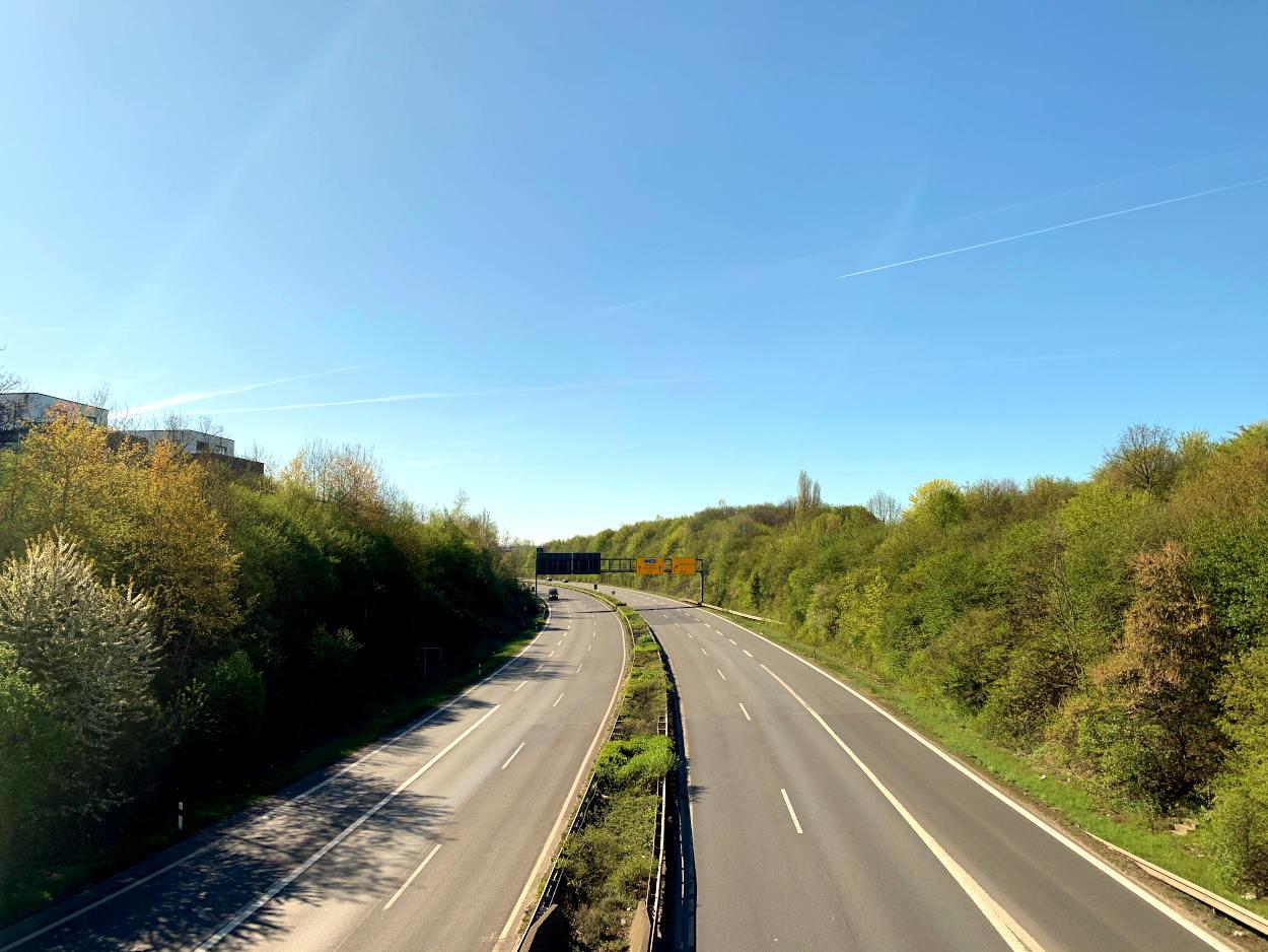Bundesstraße mit Mittelstreifen, links und rechts je zwei Spuren, nur ein Auto.