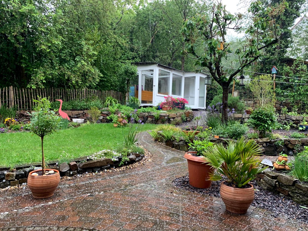 Garten, im Hintergrund Gewächshaus, kleine Hagelkörner