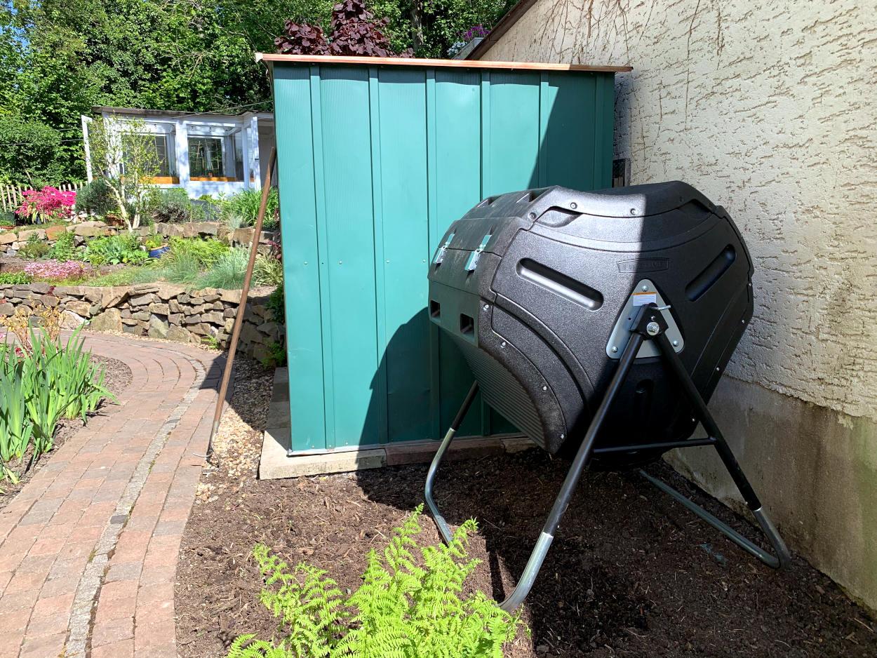 Trommelkomposter neben Gartenhäuschen