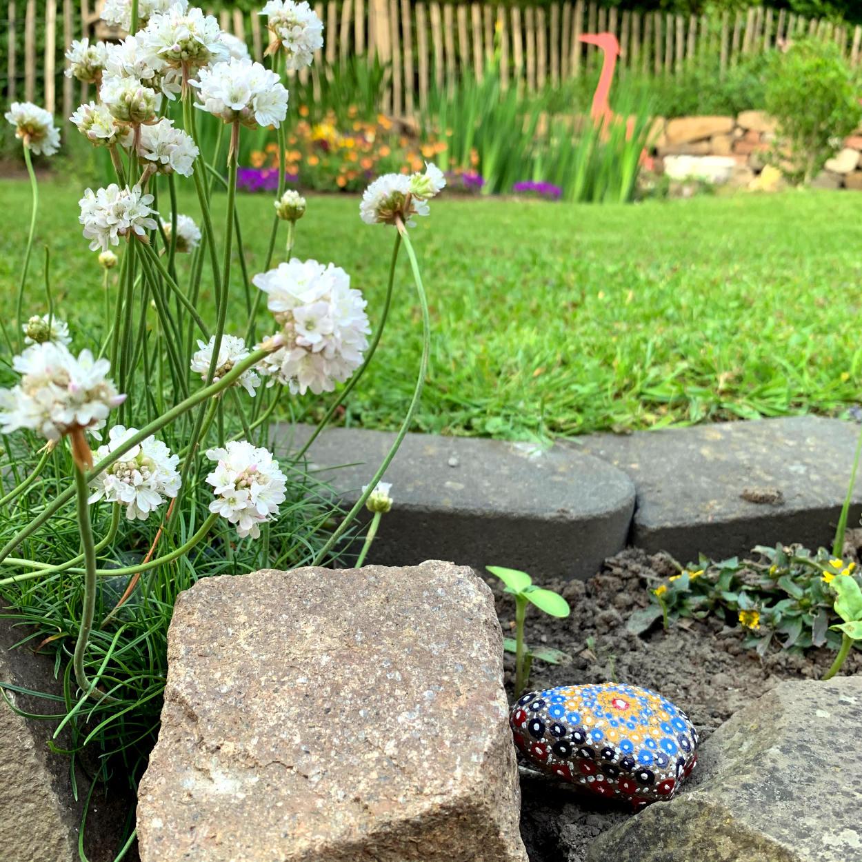 Mit Pünnktchen bemalter Stein im Gartenbeet