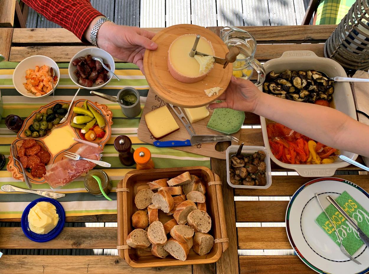 Ein mit Tapas gedeckter Tisch aus der Vogelperspektive. In der Mitte treffen sich zwei Arme und übergeben Käse.
