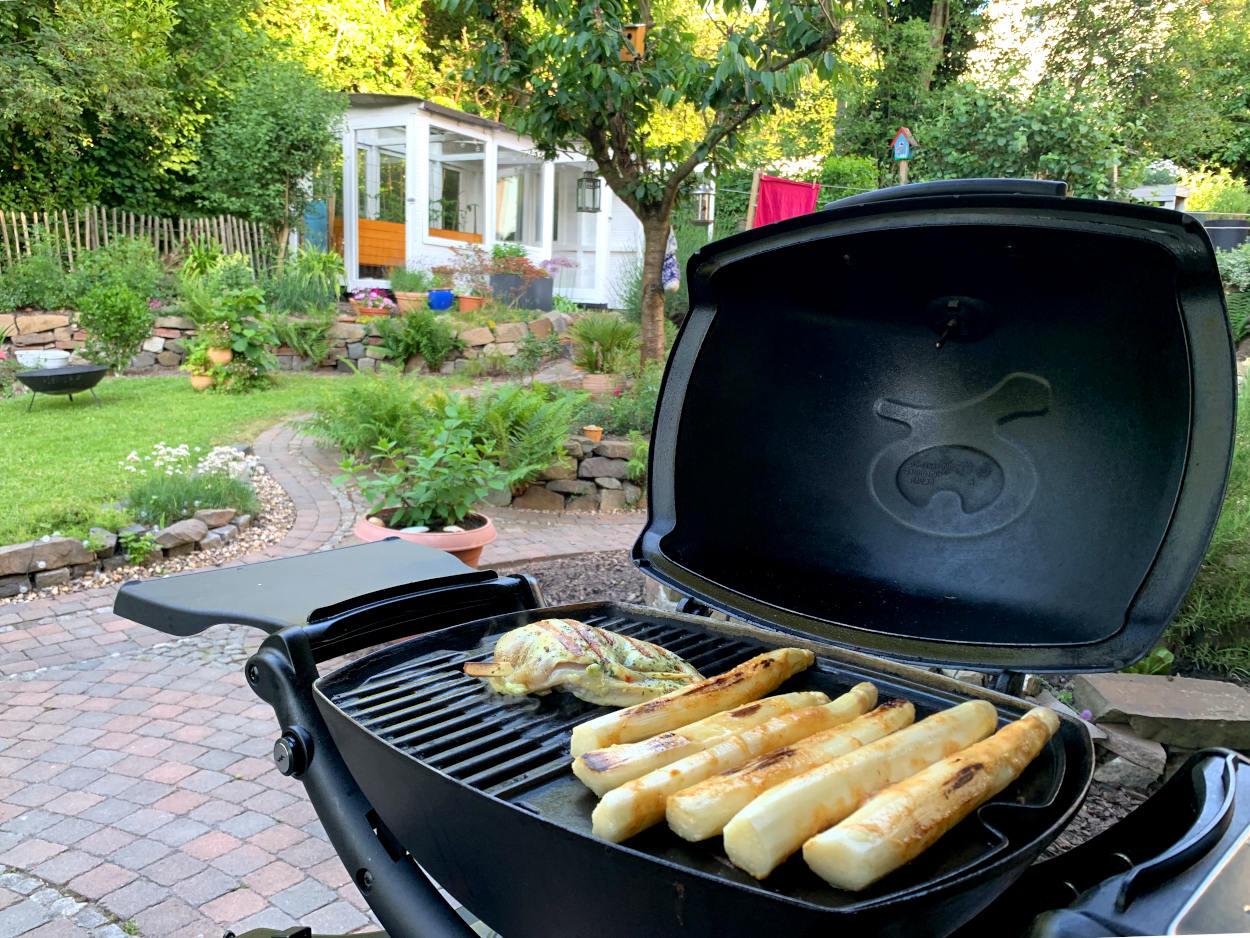 Grill mit Spargel und einem Stück gefüllter Hähnchenbrust