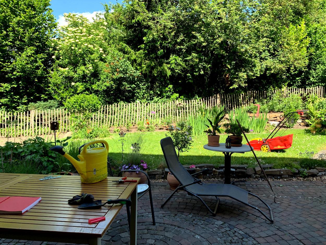 Terrasse mit allerlei Kram auf dem Tisch, unter anderem eine Gießkanne, im Hintergrund der Rasen mit Rasenmäher