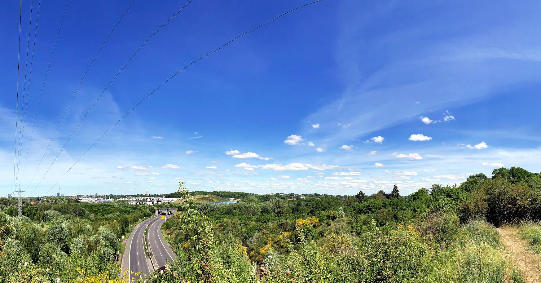 Panoramabild: Landschaft, darin eine zweispurige Straße, die unter der Fotografin durchführt, in der Ferne Großstadt. Blauer Himmel, Schäfchenwolken.