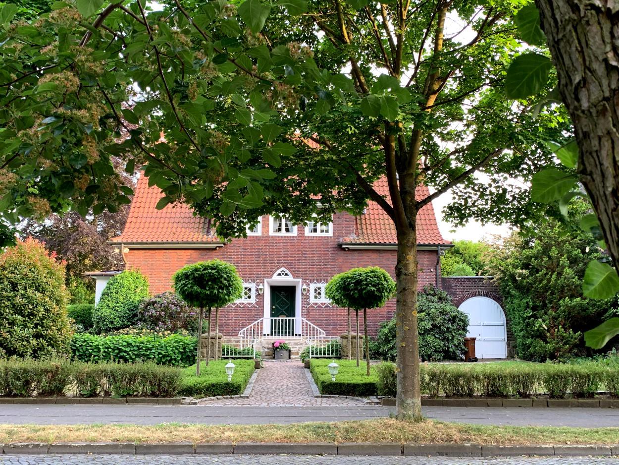 Backsteinhaus mit weiß abgesetzten Fenstern, davor Bäume