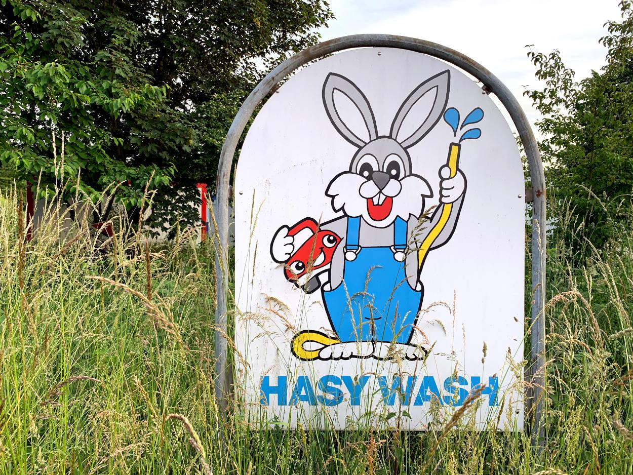 """Schild: Gemalter Hase mit Gartenschlauch und Auto unterm Arm. Schrift: """"Hasy Wash"""""""