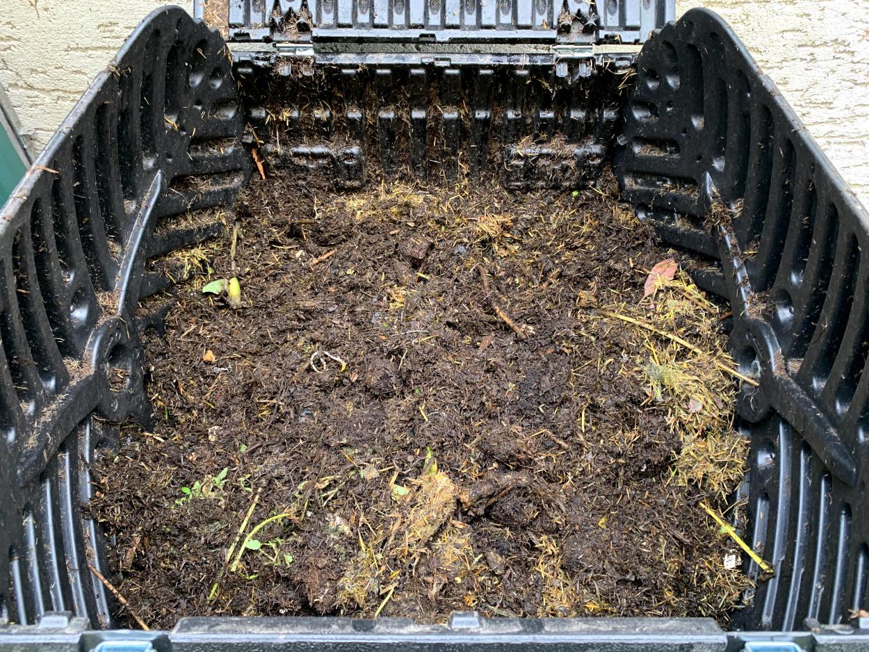 Foto aus dem Inneren des Komposters. Viel braun, bisschen gelber Rasen.