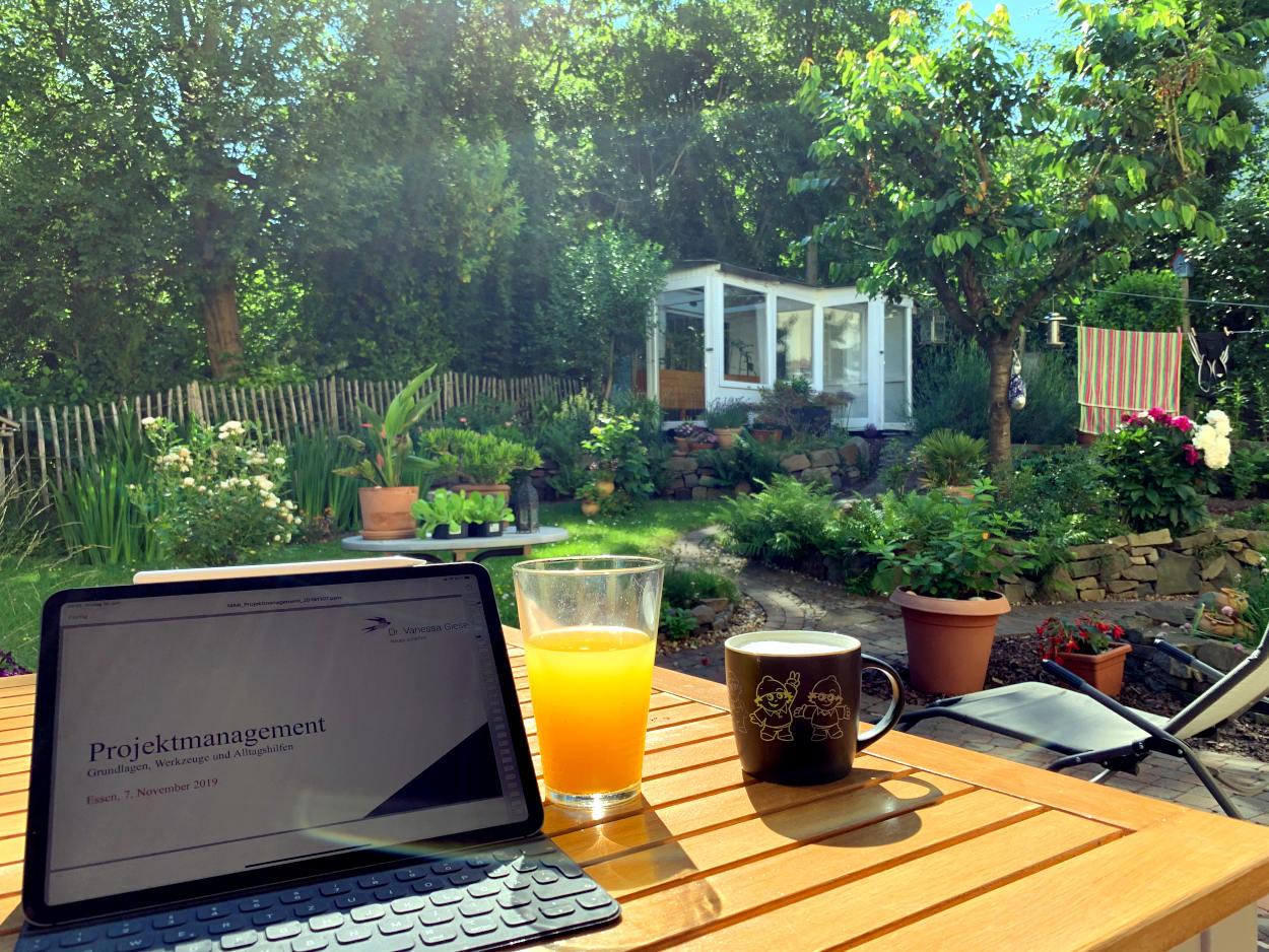 """iPad mit Folien """"Projektmanagement"""", Becher Kaffee, ein Saftglas, dahinter der Garten mit Gewächshaus"""