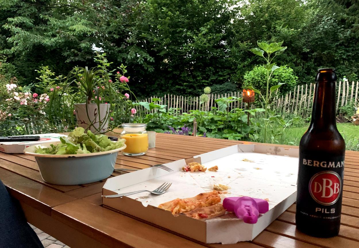 Terrassentisch mit Pizzakartons, Flasche Bier, Salat, im Hintergrund Garten mit einer Fackel