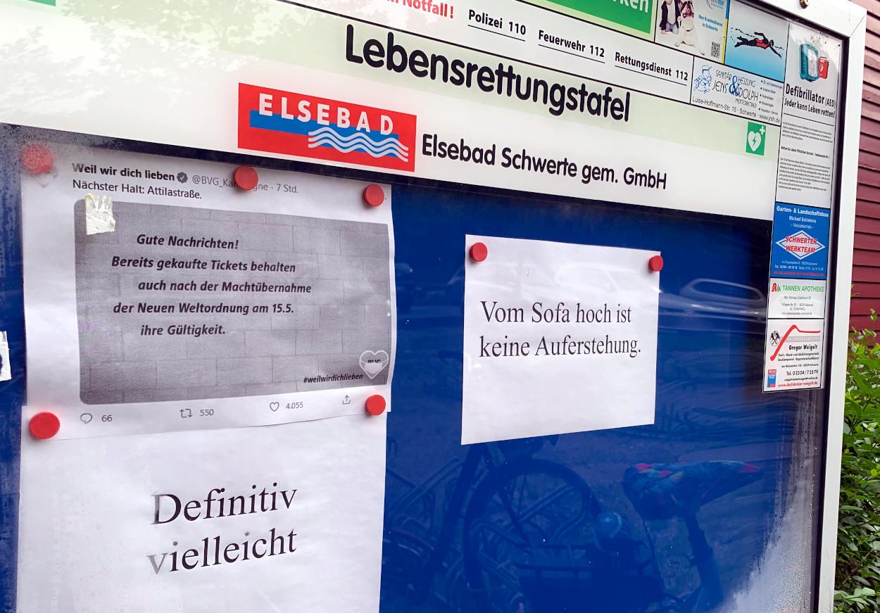 """Schaukasten mit Zetteln """"Vom Sofa hoch ist keine Auferstellung"""", """"Gute Nachrichten! Bereits gekaufte Tickets behalten auch nach der Machtübernahme der neuen Weltordnung am 15.5. ihre Gültigkeit."""""""