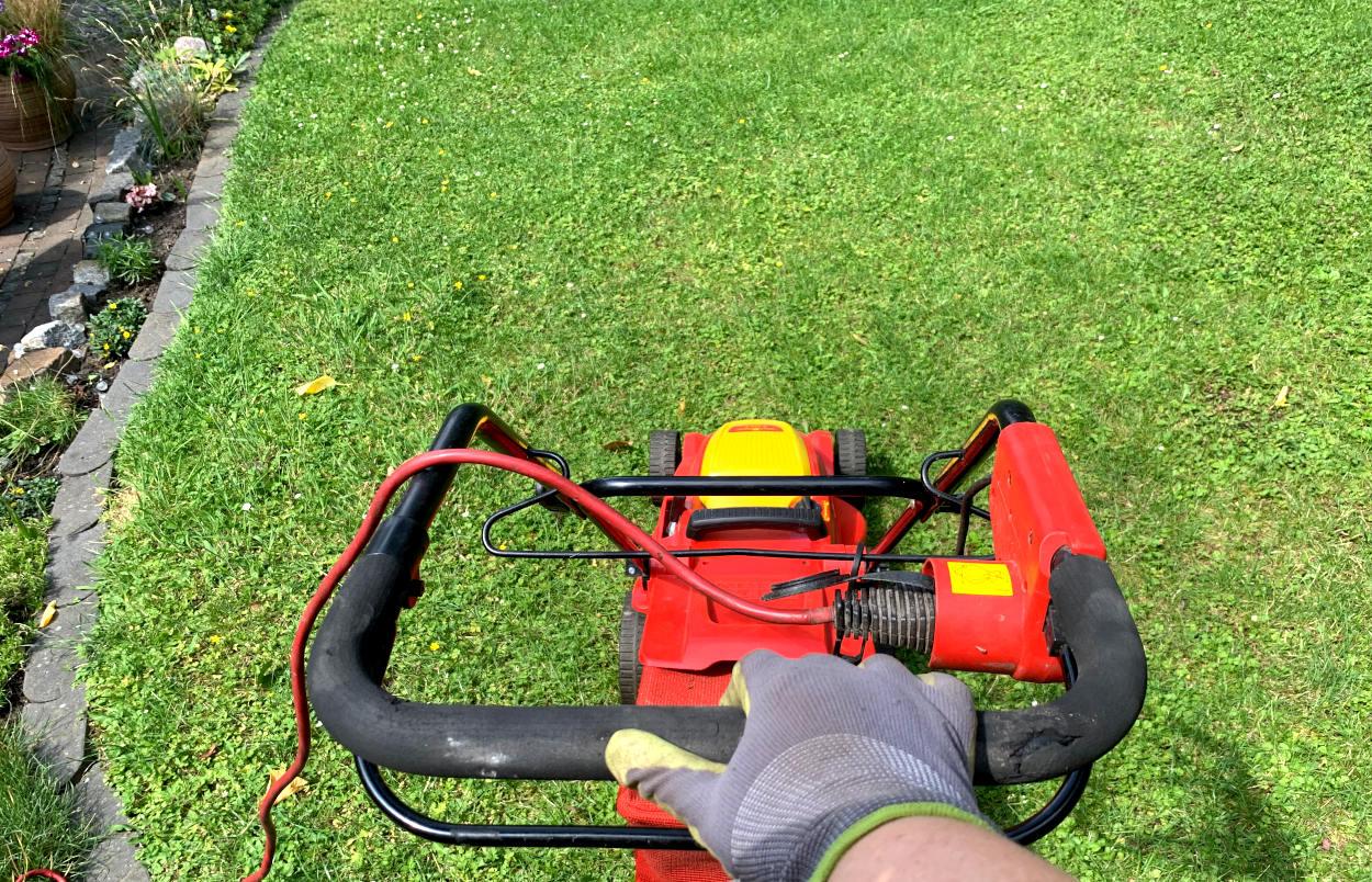 Hand am Rasenmäher