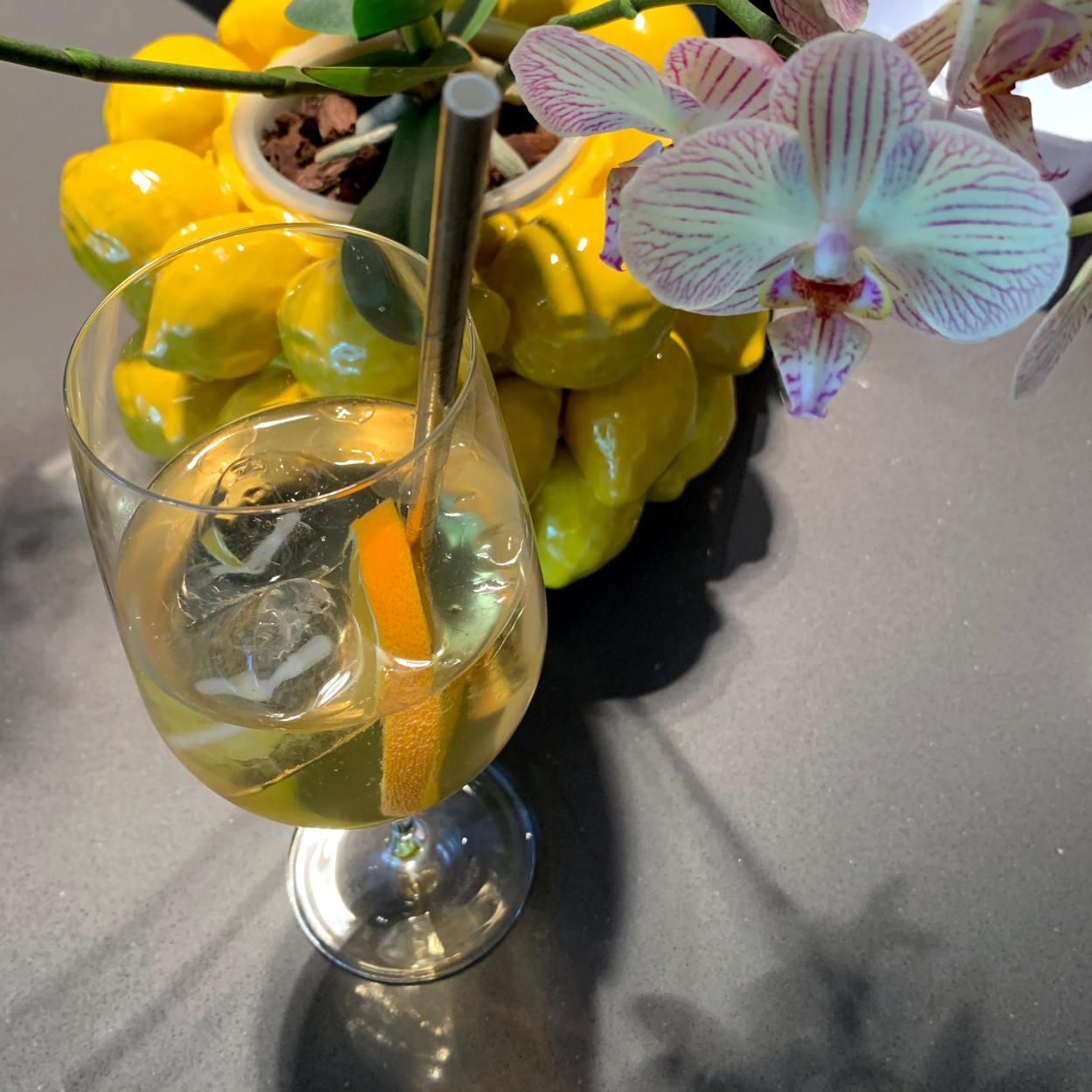 Weinglas mit heller Flüssigkeit, Eiswürfeln, Orangenscheibe, daneben eine Orchidee